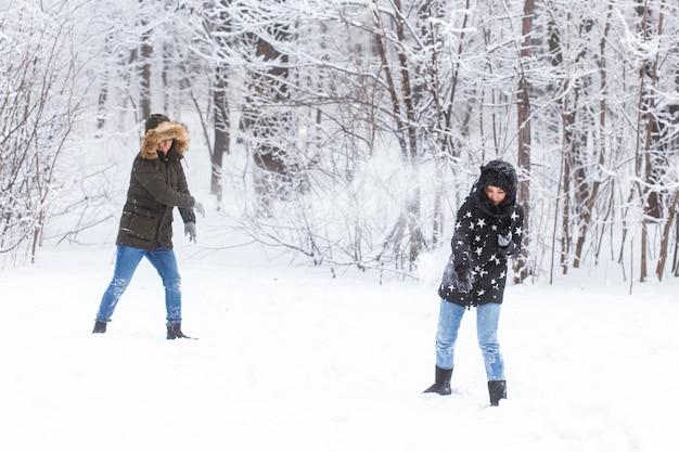재미, 계절 및 레저 개념 - 사랑 부부는 눈 위에서 겨울 나무를 재생합니다.