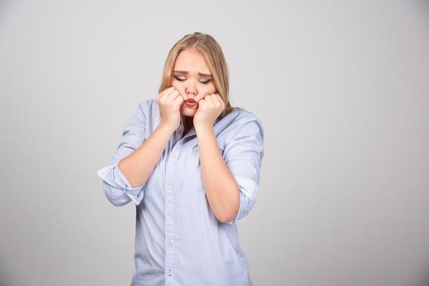 ブロンドの髪と灰色の壁に対してポーズをとって膨らんだ頬を持つ楽しい恥ずかしがり屋の女性。