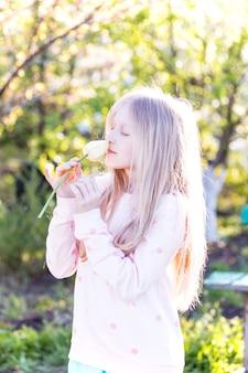 楽しい春。手に黄色のチューリップを持つ小さなブロンドの女の子の肖像画