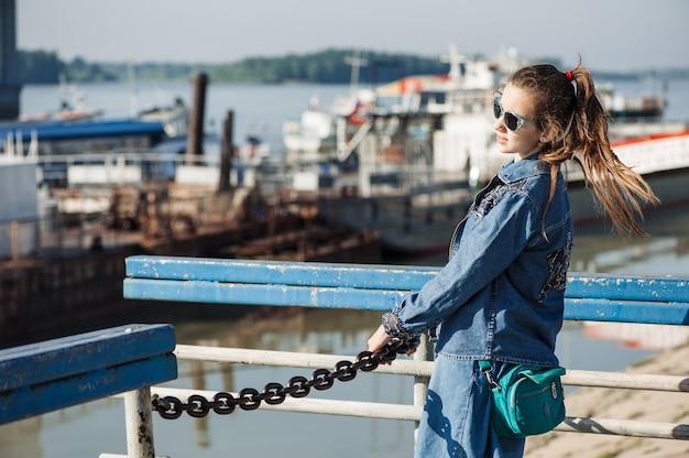 Весело девочка-подросток в синем джинсовом платье гуляет на речном вокзале. лужа молодого жизнерадостного ребенка в речном порту. девушка в солнечных очках держится на цепи.