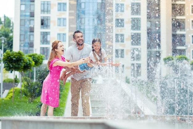 즐거운 시간. 분수 근처에 서있는 동안 딸과 놀고 기뻐하는 행복한 부모