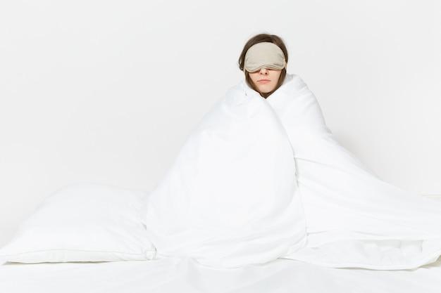 Весело усталая молодая женщина, сидящая в постели с маской для сна, простыней, подушкой, завернувшись в одеяло, изолированное на белой стене