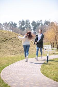 一緒に楽しんでください。晴れた春の日に自然の中で余暇を過ごす長い生姜髪の陽気な気配りのある男女