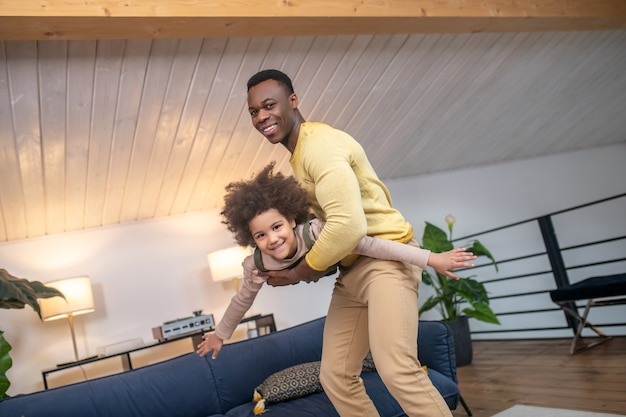 Fun with dad. cheerful young darkskinned strong dad and little cute daughter spending active leisure time at home in modern room