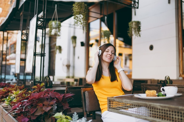Веселая женщина в уличном кафе на открытом воздухе сидит за столом в желтой одежде и слушает музыку в наушниках