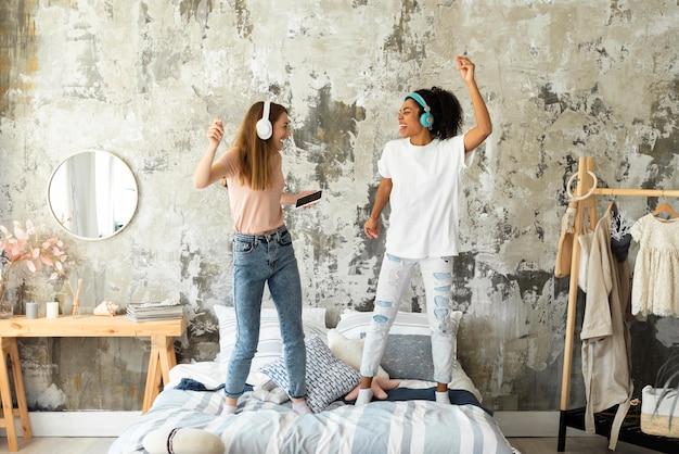 Весело женщины танцуют вместе на кровати