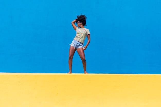 Fun young afro american woman laughing and dancing outdoors