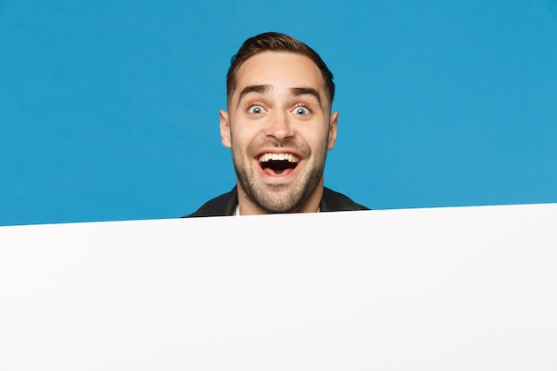 Fun young bearded man look out big white empty blank billboard for promotional content isolated on blue wall background studio portrait. people sincere emotions lifestyle concept. mock up copy space.