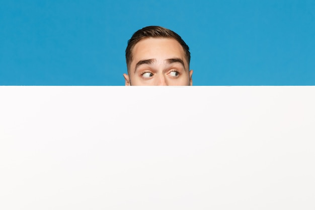 Fun young man hiding, look out eyes big white empty blank billboard for promotional content isolated on blue wall background studio portrait. people emotions lifestyle concept. mock up copy space.