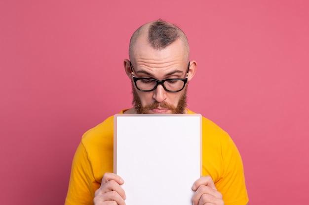 楽しい若い男は、プロモーションコンテンツの隔離されたスタジオショットのために目を白い空の空白の看板を見てください