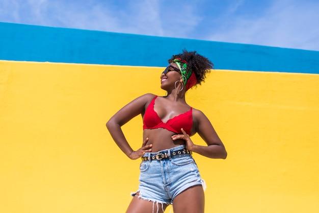 Fun молодая афро американская женщина смеется и танцует на открытом воздухе