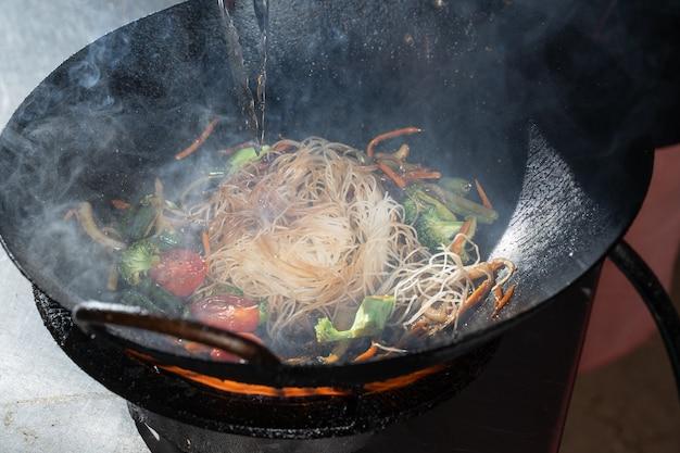 웍 팬에 불에 요리하는 야채와 함께 Funchoza Flambe 쌀 국수. 길거리 음식. 프리미엄 사진