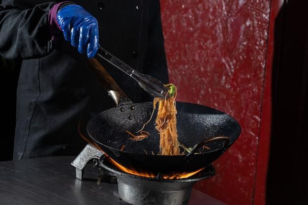 웍 팬에 불에 요리하는 야채와 함께 funchoza flambe 쌀 국수. 길거리 음식.