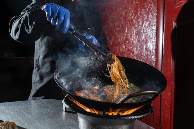 냄비 팬에 불에 요리하는 야채와 함께 funchoza 쌀 국수. 거리 flambe 음식.