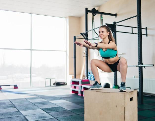 機能的でモダンなトレーニング。若いブロンドの女性は背の高い木箱にスクワットでジャンプします