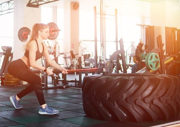 ファンクショナルトレーニング。彼女の手でハンマーで大きなゴム製の車輪を打つスポーツウェアの若いブロンドの女性。クロストレーニング