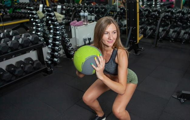 ファンクショナルトレーニング。ボディービルとフィットネス。現代のジムで薬のボールでスクワットを練習している若い陽気な女性