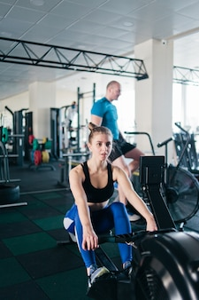 Functional training concept. sport man and woman doing exercise in simulator rowing machine and air bike at gym
