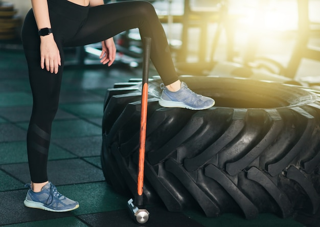 Концепция функционального обучения. время для перерыва. обрезанное фото женских ножек, большого колеса, молотка в тренажерном зале.