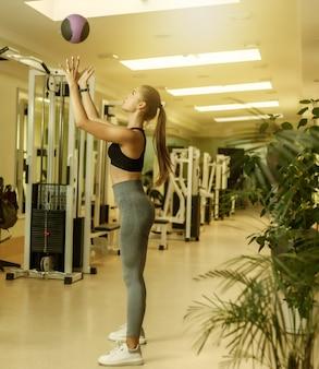 ファンクショナルトレーニングのコンセプト。スポーツウェアの若いフィットの女性がジムで薬のボールを投げる
