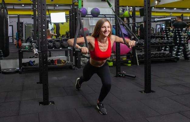 기능 훈련. 건강한 라이프 스타일 개념입니다. trx 스트랩으로 운동을 하는 날씬한 여성. 체육관에서 서스펜션 트레이너와 함께 운동하는 젊은 여성