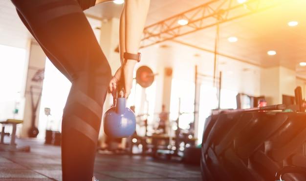 ケトルベルを使ったファンクショナルトレーニング。ジムでケトルベルと運動をしているクローズアップの女性