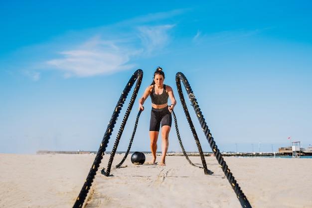 ビーチでのファンクショナルトレーニングトレーニング、屋外でスポーツをしている健康でアスリートの女性