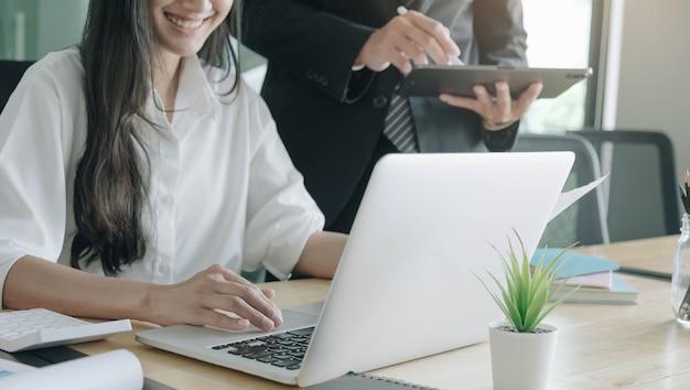 펀드 매니저 팀 컨설팅 및 디지털 태블릿으로 투자 주식 시장 분석에 대해 논의합니다.