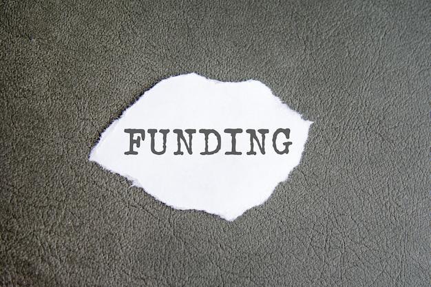 Финансирование знак на рваной бумаге на сером фоне.