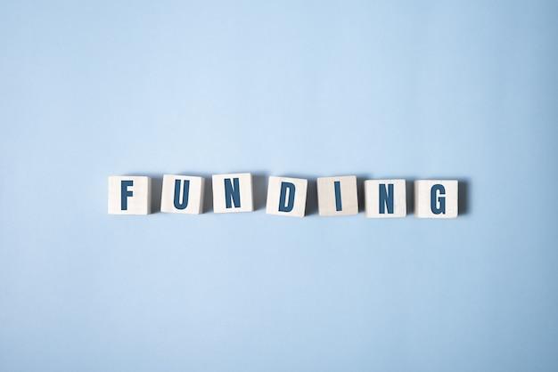 Финансирование слово написано на деревянных кубиках на синем.