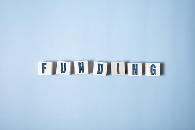 Funding word written on wooden cubes on blue.