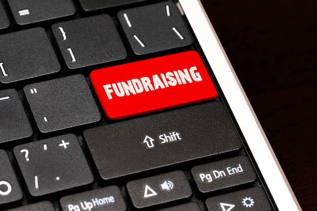 黒のキーボードの赤のenterボタンで募金活動。
