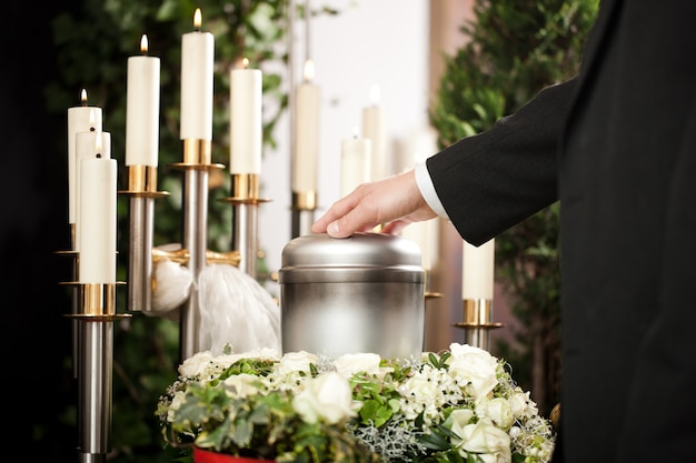 Funeral urn with candles and flowers