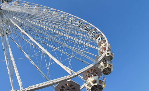 Funfair ferris wheel on blue sky background.