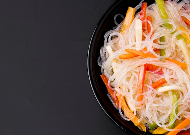 Fungose noodles with vegetables on a black background next to hot pepper. there is a place for text.