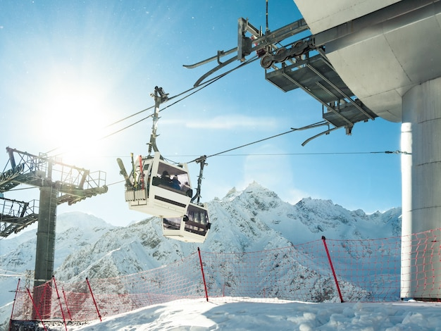 Funicular or cable cars with skis and snowboards at winter mountains background in ski resort