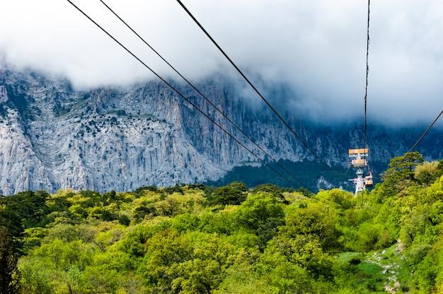 ケーブルカーの道は美しい茂みの背景の山々を通り過ぎます