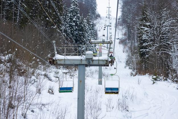 케이블카는 겨울 서리가 내릴 때 눈으로 덮인 언덕이 많은 산과 나무 사이에 있습니다. 개념 노르딕 컨트리 휴가 및 스키 관광