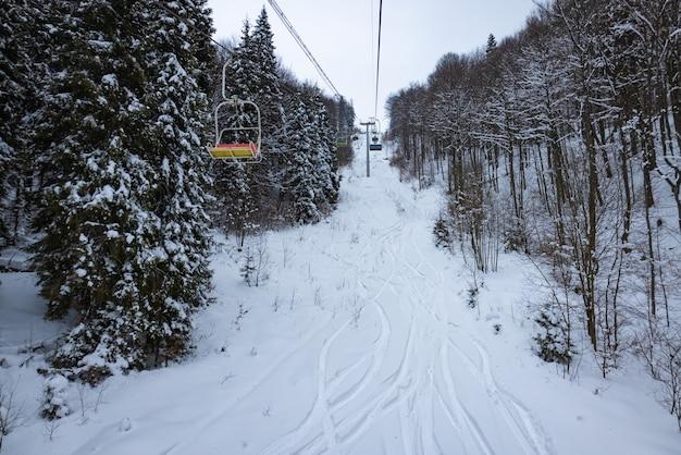 ケーブルカーは、冬の凍るような時期に雪に覆われた丘陵の山々と木々の間にあります。コンセプト北欧のカントリーバケーションとスキーツーリズム
