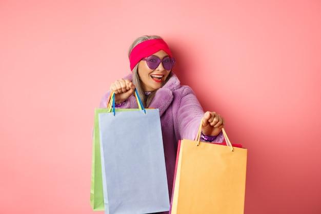ファンキーでクールなアジアの年配の女性がおしゃれな服を着て、買い物に出かけたり、ショップの紙袋を持ったり、ピンクの背景を楽しんだりしながら踊ります