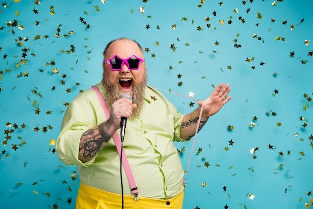 ファンキーなひげを生やした太った男が青い背景のマイクで曲がりくねって歌う