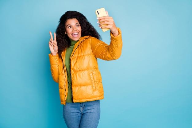 ファンキーな暗い肌の巻き毛の女性電話を保持しているselfiesを示すvサインのシンボルを着用トレンディな黄色の秋のオーバーコートジーンズ緑のセーター孤立した青い色の壁