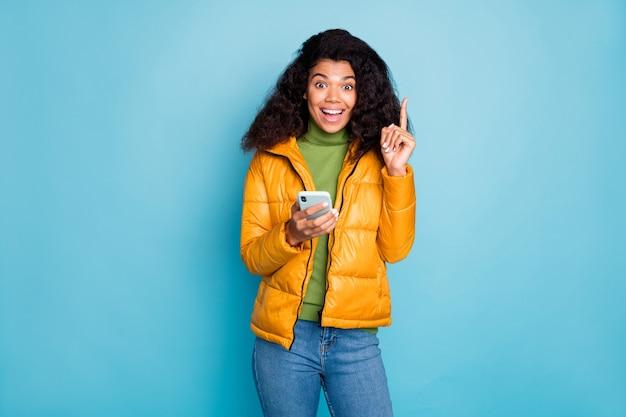 ファンキーな暗い肌の巻き毛の女性が人差し指を上げる電話を上げるクールな創造的なポスト思考を着る黄色のオーバーコートジーンズ緑のセーター孤立した青い色の壁