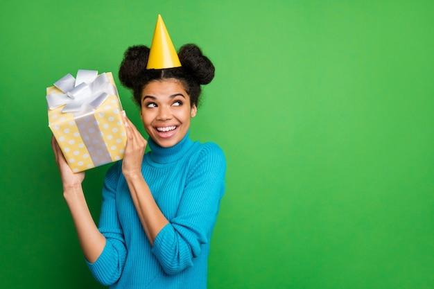 ファンキーな暗い肌の女性の誕生日は興奮した耳の近くに大きなギフトボックスの手を保持します