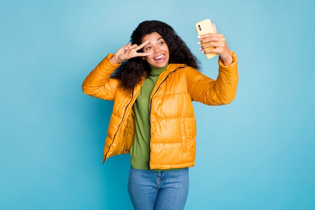 Funky dark skin lady hold telephone make selfies show v-sign stick tongue out mouth wear trendy yellow fall overcoat jeans green sweater isolated blue color wall