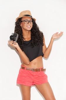 カメラを持つファンキーな女の子。眼鏡とファンキーな服を着てカメラを保持し、白い背景に立っている間身振りで示す陽気な若いアフリカの女性