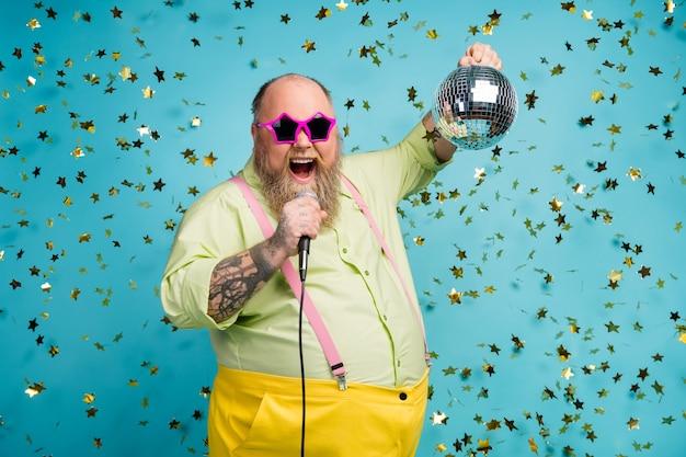 ファンキーな男は、落ちてくる蛇紋石と青い背景のマイクで歌うディスコボールを保持します