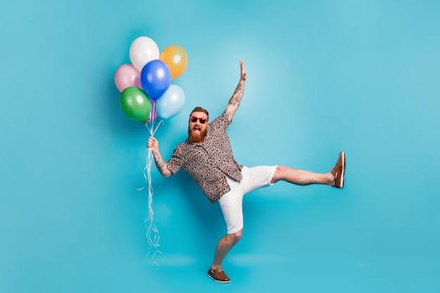 Напуганный рыжий бородатый турист держит кучу воздушных шаров