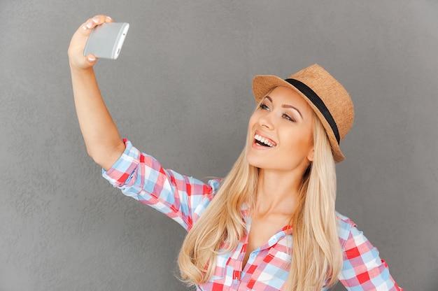Funky selfie. cheerful young woman making selfie on her smart phone
