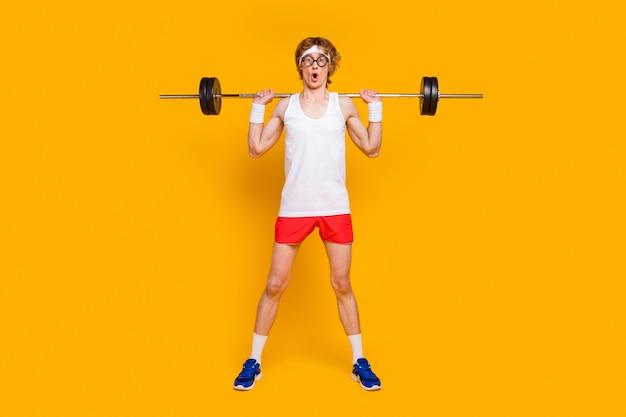 Веселый стройный спортивный парень поднимает штангу